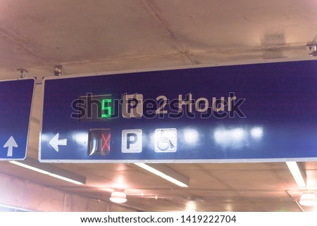 Overhead neon sign at indoor  airport parking lot displays number of available parking spaces. Available empty spots display counter information. 2 hour parking limitation #1419222704