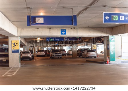 2 hour parking overhead neon sign at indoor airport parking lot displays number of available parking spaces. Available empty spots display counter information #1419222734