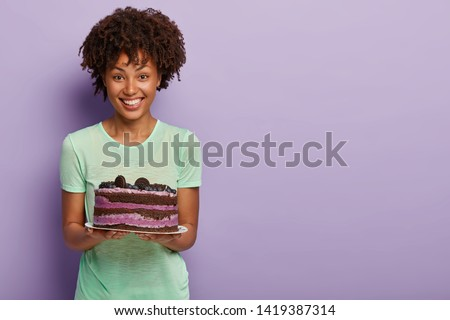Happy Afro American woman holds delicious birthday cake with blueberry, treats guests with tasty sweet dessert, dressed in casual green t shirt, stands in studio against purple background, free space #1419387314