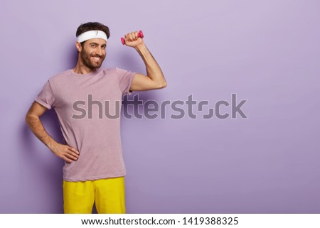 Glad smiling male gymnast keeps one hand on waist, raises muscualr arm with dumbbell, satisfied after having training in gym, dressed in casual t shirt and shorts isolated over purple wall empty space #1419388325