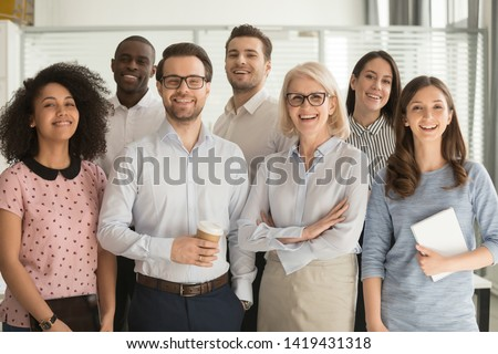 Smiling multiethnic employees standing looking at camera making team picture in office together, happy diverse work group or department laugh posing for photo at workplace, show unity and cooperation