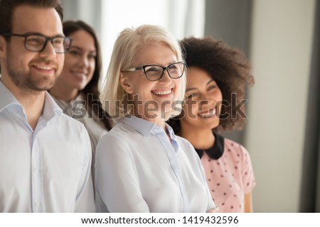 Side view of smiling diverse employees stand in row together posing for group picture in office, happy confident multiethnic team look at camera making photo, showing unity. Teamwork concept #1419432596