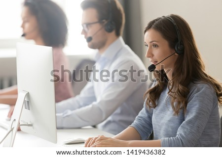 Millennial female call center agent wear headset with microphone consult customer online on pc in coworking space, focused woman employee in earphones busy working on computer in shared office #1419436382