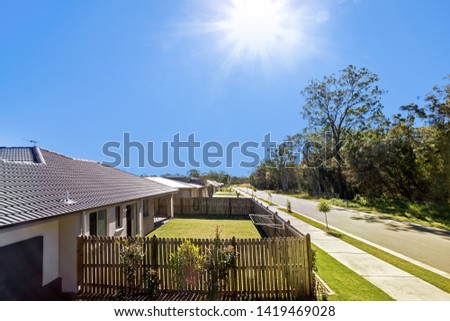 A house exterior featuring a garden and a wooden boundary #1419469028