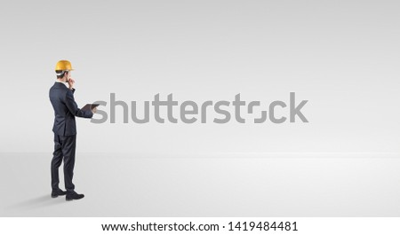 Young architect with construction helmet standing in an empty space and holding a plan #1419484481