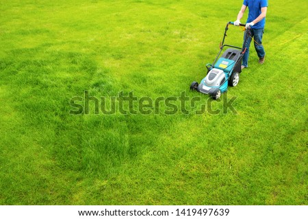 A lawn mower is cutting green grass, the gardener with a lawn mower is working in the backyard, a side view. #1419497639