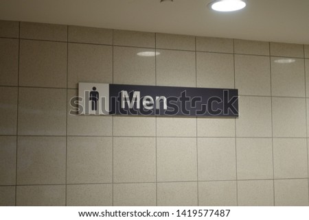 A sign signifying a men's bathroom or lavatory entrance.