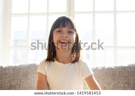 Happy cute preschooler girl sit on couch talking on web cam  conversation, funny little child vlogger shoot vlog speak chat with subscribers, smiling small kid record video on sofa at home #1419581453