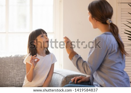 Young mom and little preschooler daughter at home learn sign language together, female nanny or teacher talk nonverbal with small disabled kid, practice sounds and signs making gestures #1419584837