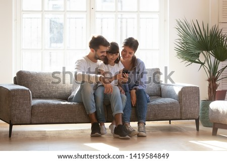 Smiling young family with preschooler child have fun using smartphone relaxing on couch, happy little girl hold cellphone play game enjoy spending time at home, rest on sofa with mom and dad