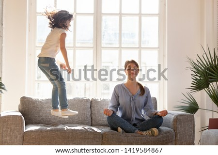 Young mom sit on couch at home meditating in lotus position, small daughter have fun jumping near, concentrated calm mother practice yoga relax on sofa ignore playful kid. Stress free concept Royalty-Free Stock Photo #1419584867