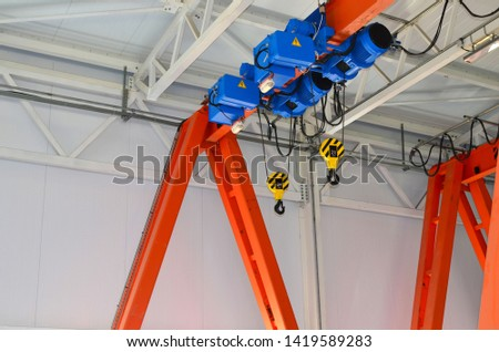 Bridge lifting Crane Hook with electric engines on the background of the industrial workshop production plant. The concept of a heavy manufacturing process at an industrial factory - Image #1419589283