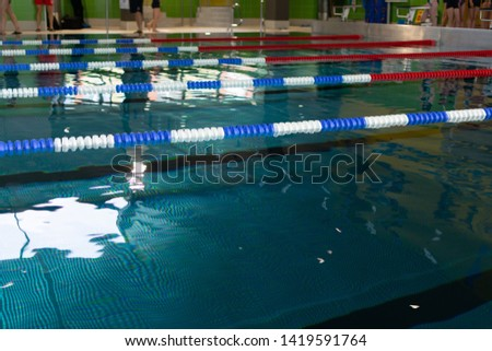 Swimming sport event. Splashed water in the pool during competitions with children, adolescents and adults. #1419591764