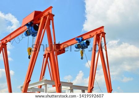 Bridge lifting Crane with Hooks on the background blue sky.The concept of a heavy manufacturing process at an industrial factory, background, texture - Image #1419592607