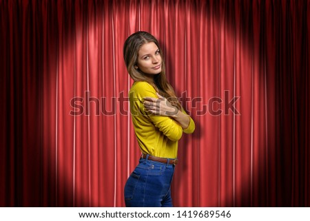 Young woman wearing blue jeans and yellow shirt embracing herself on red stage curtains background. Digital art. Feelings and emotions. Gestures and body language. #1419689546