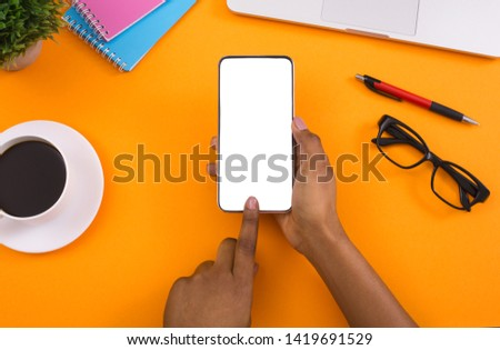 Photography editing. African-american woman using blank smartphone, preparing content for social media, orange background, free space