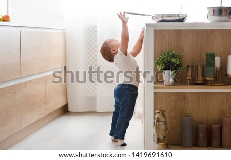 Child safety at home concept. Little baby reaching for hot pan on stove in kitchen, empty space Royalty-Free Stock Photo #1419691610