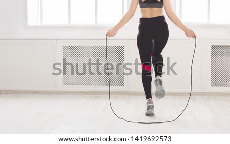 Unrecognizable woman jumping over the skipping rope in studio, crop, panorama, free space Royalty-Free Stock Photo #1419692573
