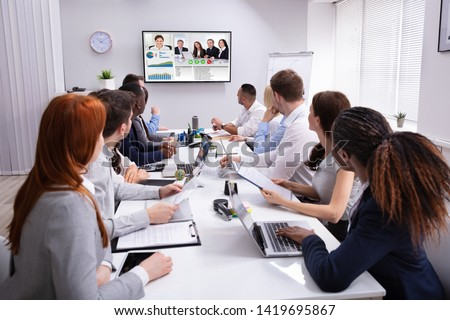Group Of Businesspeople Having Video Conference With Another Business Team In Office Royalty-Free Stock Photo #1419695867