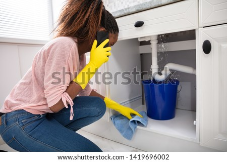 Close-up Of A Young Woman Placing Blue Bucket Under Water Leaking From Sink Pipe Royalty-Free Stock Photo #1419696002