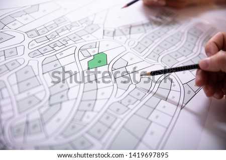 Close-up Of Human Hand Holding Pencil Over Paper Cadastre Map Royalty-Free Stock Photo #1419697895