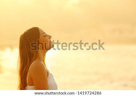 Side view portrait of woman at sunset relaxing breathing fresh air deeply on the beach #1419724286