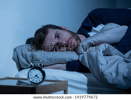 Sleepless and desperate young caucasian man awake at night not able to sleep, feeling frustrated and worried looking at clock suffering from insomnia in stress and sleeping disorder concept. #1419779672