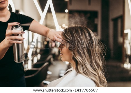 Beautiful young woman with long curly hair in hair salon. Professional hairdresser styling with hairspray. Royalty-Free Stock Photo #1419786509