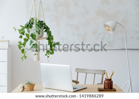 Stylish and boho home interior of living room with wooden desk, laptop, white lamp, macrame shelf and desk supplies. Design and elegant accessories. Modern home decor. Abstract painting on the wall.  #1419886289