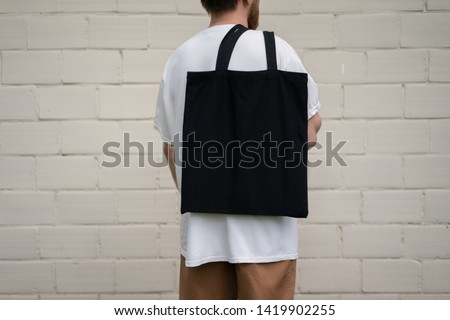 Urban mockup of tote bag. Men holding black cotton tote bag on a brick wall background. Template can be used for you design  Royalty-Free Stock Photo #1419902255