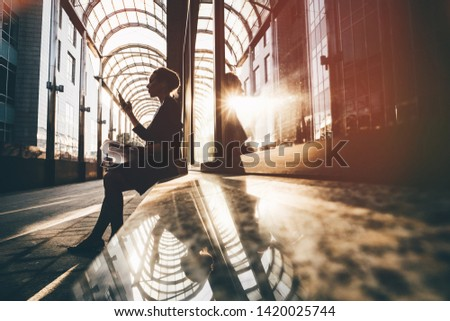 Silhouette of young businesswoman looking at the phone near the modern office building. Royalty-Free Stock Photo #1420025744