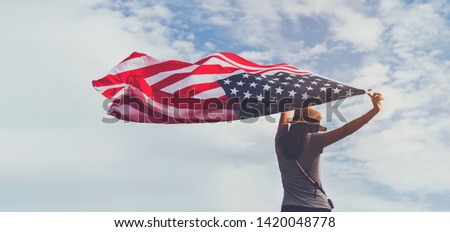 Young woman holding American flag on blue sky background with copy space.Vintage tone.Concept of America celebrate 4th of July. Royalty-Free Stock Photo #1420048778
