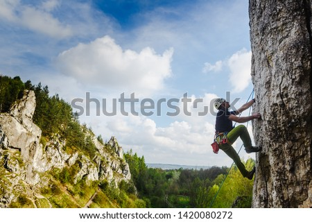 Young male climber hanging by a cliff Royalty-Free Stock Photo #1420080272
