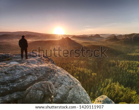 Man on the rock empire with hands in trousers pocket  watch over the misty morning valley to rising sun at horizon. #1420111907