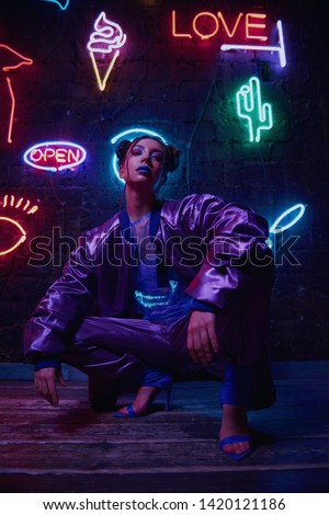 Cyberpunk style portrait of girl in futuristic purple sportswear. She poses against wall of neon figures. Set is lit with magenta light. Clothes is oversized. Picture has dark noir tones. #1420121186