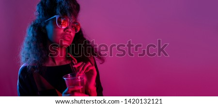 Fashion young african girl black woman wear stylish pink glasses holding drink looking at camera isolated on party purple studio background, horizontal banner for website design, portrait, copy space