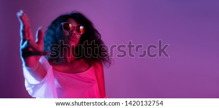 Fashion young african girl black woman wear stylish pink glasses dance look at camera shoot hand gun isolated on party disco purple studio background, banner for website design, portrait, copy space #1420132754