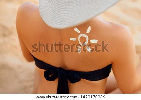Sun cream on tanned shoulder with sun shape . Sun protection. Beautiful woman in bikini applying  Solar Cream. Skin and body care.Portrait of female holding suntan lotion and moisturizing sunblock. #1420170086