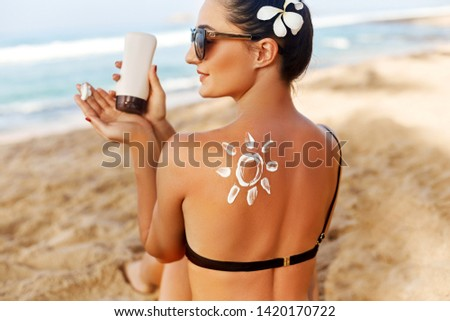 Beauty Woman Applying Sun Cream  on Tanned  Shoulder In Form Of The Sun. Sun Protection.Sun Cream. Skin and Body Care. Girl Using Sunscreen to Skin. Female Holding Suntan Lotion #1420170722
