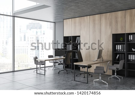 Modern office corner with gray walls, tile floor, panoramic window, wooden bookcase with folders and rows of computer desks with chairs for clients. 3d rendering #1420174856