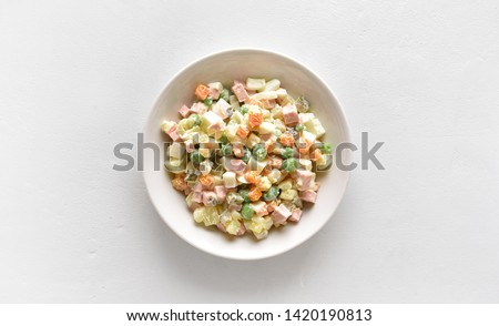 "Traditional russian salad ""Olivier"" from boiled vegetables and sausage with mayonnaise in bowl. Russian New Year or Christmas salad on light background with copy space. Top view, flat lay #1420190813"