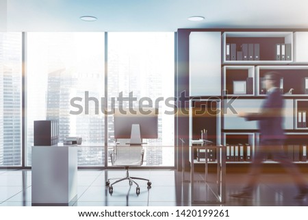 Businessman walking in panoramic CEO office with black walls, white bookcase and glass computer table. Toned image blurred #1420199261