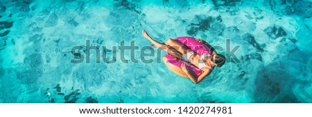 Beach vacation woman relaxing in pool float donut inflatable ring floating on turquoise ocean water background in Caribbean travel summer banner panorama. Girl in white bikini top drone view. #1420274981