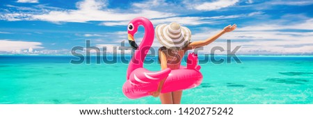 Happy summer vacation fun woman tourist enjoying travel holidays on beach banner background ready for swimming pool with flamingo float - funny holiday concept. #1420275242