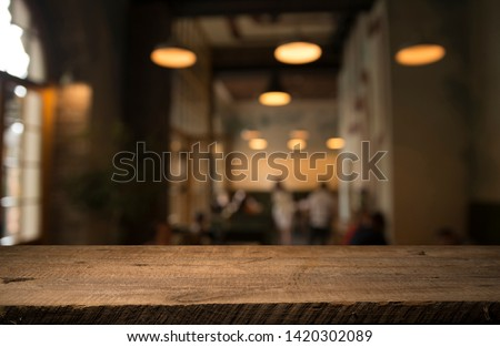 image of wooden table in front of abstract blurred background of resturant lights #1420302089