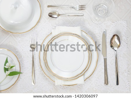 Beautifully decorated table with white plates, crystal glasses, linen napkin and cutlery are on luxurious tablecloths; top view #1420306097