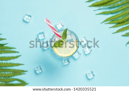 Glass of water or drink with ice, lemon and mint on a blue background with palm leaves and fern. Ice cube. Concept of hot summer, alcohol, cooling drink, thirst quenching, bar. Flat lay, top view