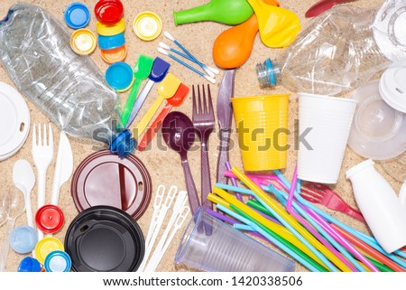 Disposable single use plastic objects such as bottles, cups, forks, spoons and drinking straws that cause pollution of the environment, especially oceans. Top view on sand #1420338506