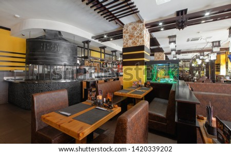 """MOSCOW - SEPTEMBER 2014: The interior of the popular modern Japanese chain of restaurants """"YAKITORIYA"""" in Moscow. Restaurant room with open kitchen #1420339202"""