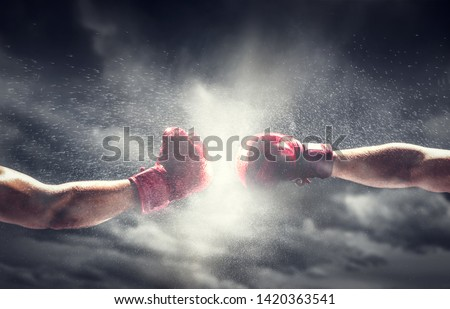 Two boxing gloves punch. Light on cloudy sky. Box, power, fight symbols. Royalty-Free Stock Photo #1420363541